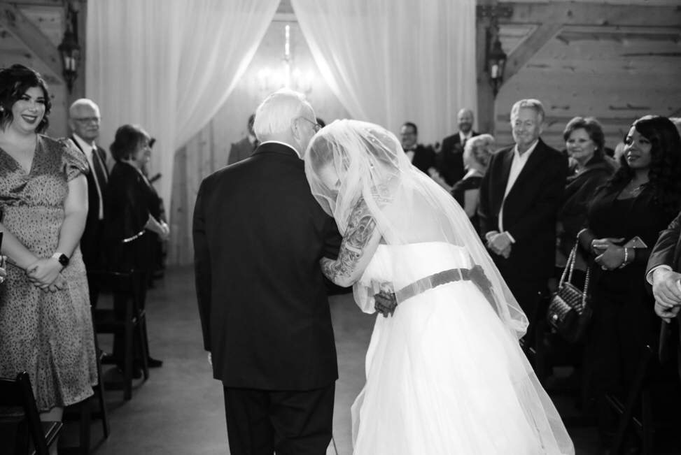 Bride and groom wedding ceremony. Bride walking down the aisle to the groom in black and white in Oklahoma City. Photo by affordable wedding photographer, Kenzie's Photography